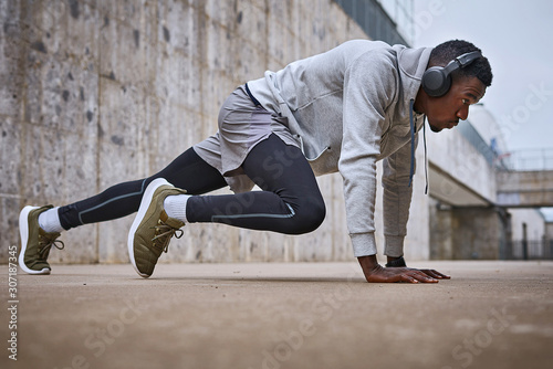 Fototapeta Athletic man is exercising near the grey wall obraz