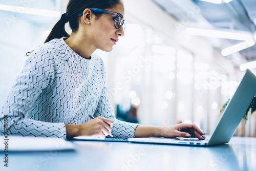 Fototapety, obrazy: Professional administrative manage in spectacles for eyes protection checking content of company website on laptop computer, serious female secretary making booking on netbook working in office