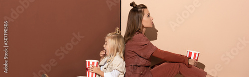 Obraz panoramic shot of daughter eating popcorn and mother on beige and brown background - fototapety do salonu