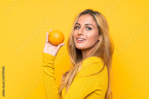 Young blonde woman holding an orange over yellow background