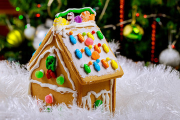 Gingerbread house in snow on decorated christmas tree background.