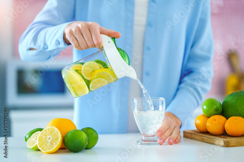Woman pouring refreshing infused detoxification citrus water from jug in a glass for vitamin detox drink. Slimming antioxidant drinks for diet healthy drinking
