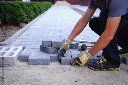 Fotografie, Obraz The master in yellow gloves lays paving stones