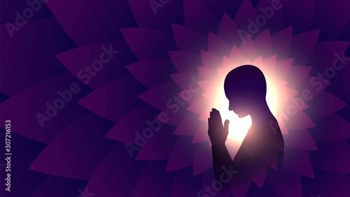Black silhouette of a praying person, a Buddhist on a background of bright light Canvas Print