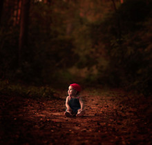 Baby In Blue Overalls And Red Hat Sitting On Ground