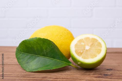 natural lemons with lemon leaves on rustic wood Wallpaper Mural
