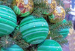 Green Christmas balls with stripes. Christmas decor in green colors.