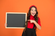 New Back To School Product. Happy Girl Point Finger At Blackboard. Little Child Presenting Product. Product Promotion. Product For Sale. Empty Blackboard For Advertising Text, Copy Space.
