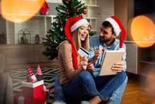 Love Couple With Christmas Hat On Head Using Tablet And Credit Card To Buying Online