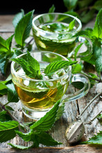 Two Glass Cups With Fresh Mint Tea On Wooden Table
