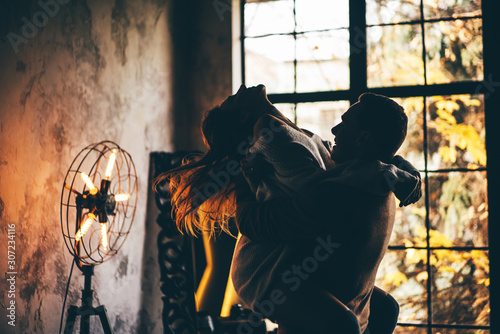 Young man holding woman in his hands. Couple in love at the home. Fotobehang