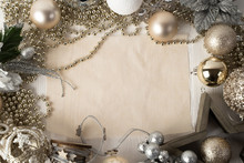 Christmas Composition Of A Wooden Star, Christmas Gold And Silver Blinders, Wooden Heart, Branches, Gold Beads On A White Natural Wooden Background With Parchment Sheets For Records In The Center.