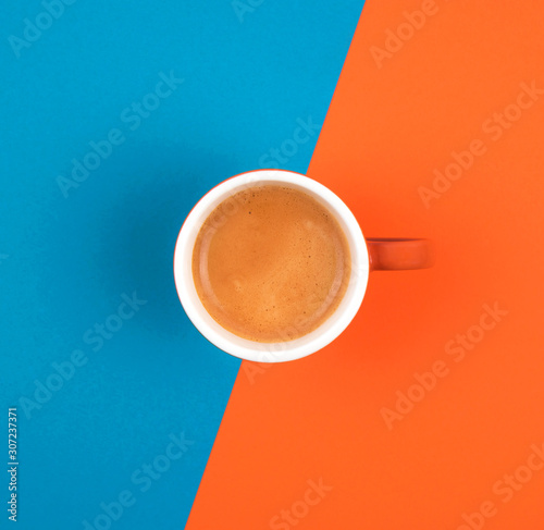 Obraz Fresh brewed coffee in ceramic cup over orange and blue background. Place for text. - fototapety do salonu