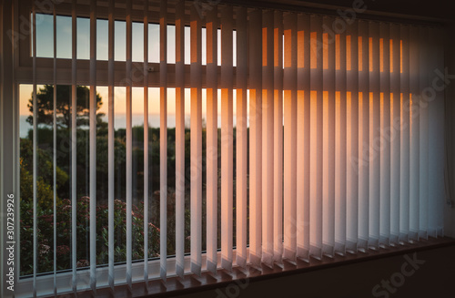 White vertical slat blinds hanging in front of a window as the sun is setting turning the light golden Wallpaper Mural
