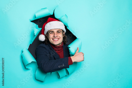 Photo  Young handsome man in santa hat pointed with hands you on copy space through green paper hole