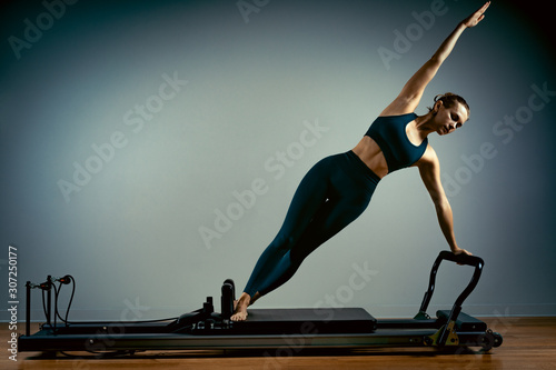 Young girl doing pilates exercises with a reformer bed. Beautiful slim fitness trainer on reformer gray background, low key, art light. Fitness concept - 307250177