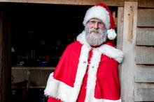 Man Wearing Santa Claus Costume Standing In Workshop Doorway, Looking At Camera.