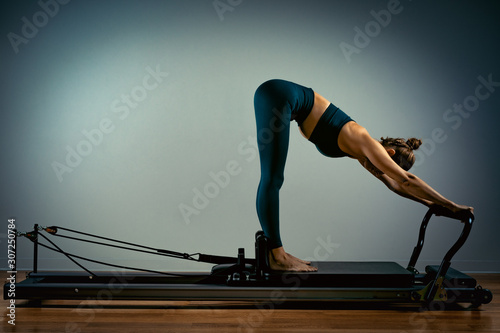 Fotografie, Obraz Young girl doing pilates exercises with a reformer bed