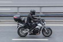 Motorcyclist In A Helmet Rides A Motorcycle On The Road.