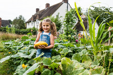 Girl Standing In A Vegetable Patch In A Garden, Holding Yellow Gourd, Smiling At Camera.