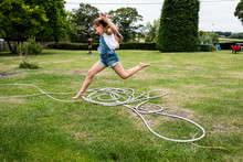 Girl Jumping Over Hose In Lawn