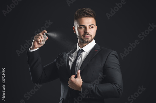 Fototapeta Handsome young man with bottle of perfume on dark background obraz