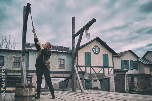 Photo  A pirate girl cuts the rope of the gallows with a cutlass in the square of the o