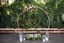 Wedding Ceremony. Beautiful Wedding Round Arch Decorated With Flowers, Greenery And Candles, Outdoors