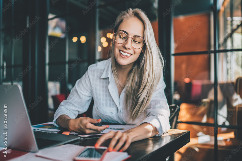 Fototapeta Cheerful freelancer checking notifications on smartphone
