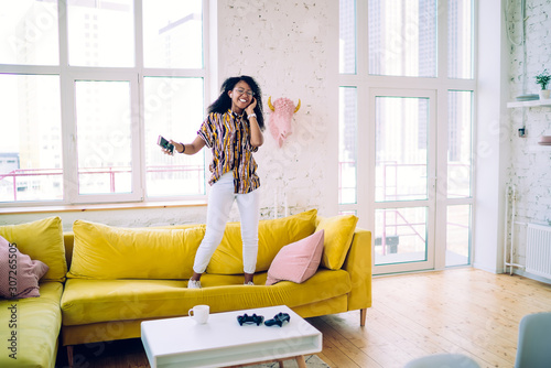Joyful African American woman standing on couch and listening to music - 307265505