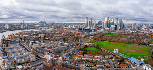 Fototapety, obrazy: London, England - Aerial Panoramic skyline view of Bank and Canary Wharf, central London's leading financial districts with famous skyscrapers at golden hour sunset during cloudy skies.