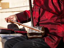 Asian Senior Man Playing An Erhu In The Street