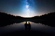 canvas print picture - Romantic Couple Standing Under The Starry Sky, Milky Way Reflects Off Lake