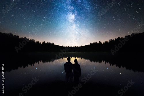 Romantic Couple Standing Under The Starry Sky, Milky Way Reflects Off Lake Fototapeta