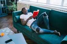 Male Relaxing On Green Sofa Wi...