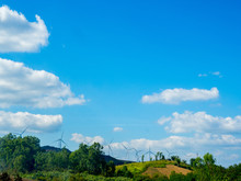 Wind Turbine Generators Line The Hilltops And Aerial Landscape With Vivid Blue Sky And Clouds Background.