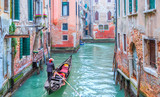 Venetian gondolier punting gondola through green canal waters of Venice Italy