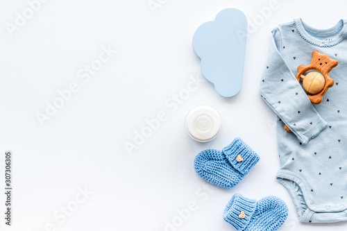 Newborn baby boy set - blue clothes as bodysuit, booties, toys - on white table top-down frame copy space