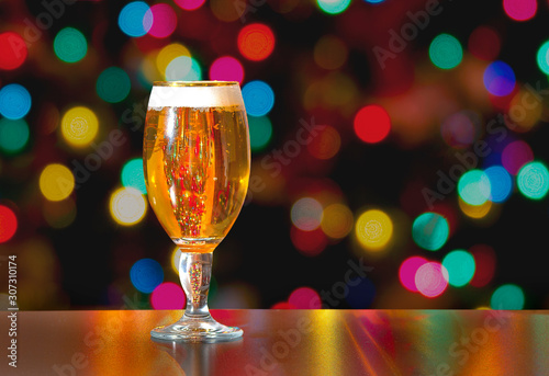 Photo A Cup of Stella Artois full of beer with holiday colorful lights in background