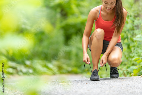 Fotografia Fitness girl getting ready to run exercise outside lacing running shoes on run path in forest