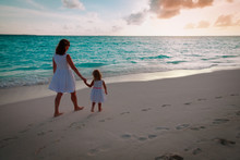 Mother And Little Girl Walking On Beach At Sunset