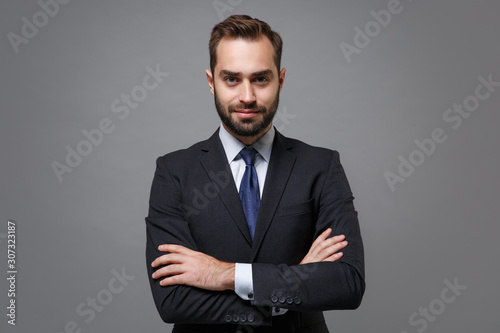 Fototapeta Attractive young business man in classic black suit shirt tie posing isolated on grey background studio portrait. Achievement career wealth business concept. Mock up copy space. Holding hands crossed. obraz na płótnie