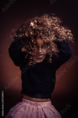 Fototapeta Studio portrait of little girl, a child playing with her long curly hair obraz