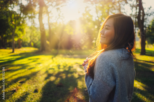 Portrait image of a beautiful asian woman standing among nature in the park befo Canvas-taulu