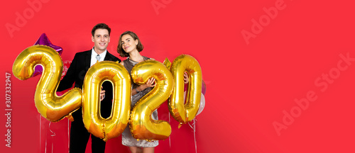 Fototapeta Lover caucasian couple celebrate and hold number golden balloon for countdown Happy New Year 2020 on 31st December together with red backdrop for banner header size and copy space obraz