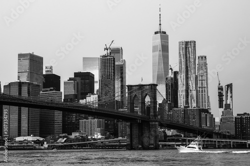 Black and white panorama of Manhattan, New York, with the Brooklyn Bridge in the foreground. Urban look wallpaper. View from Brooklyn Bridge Park.