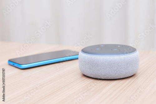 Photo amazon echo dot third generation, white, with a blue smartphone out of focus, on