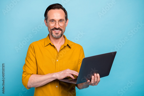 Portrait of positive cool mature man hold his computer work text type chatting with family colleagues wear good looking clothes isolated over blue color background