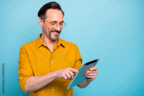 Obraz Turned photo of positive cool man tablet user search social media information feel dreamy glad expression wear stylish clothing isolated over blue color background - fototapety do salonu
