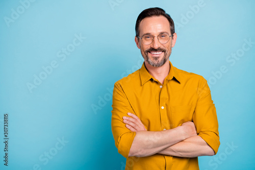 Fototapeta Portrait of charming mature man true boss feel content emotions wear yellow shirt isolated over blue color background obraz
